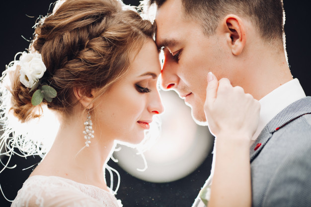 gorgeous-bride-handsome-groom-touching-by-faces-each-other_132075-2277