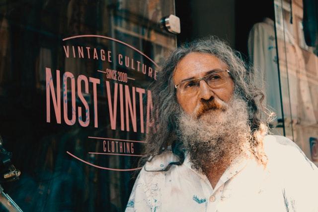 Starší muž s dlhou bradou a vlasmi stojí pred skleneným výkladom.jpg