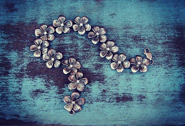 Strieborný náhrdelník z kvetou s patinou na modrom stole.jpg