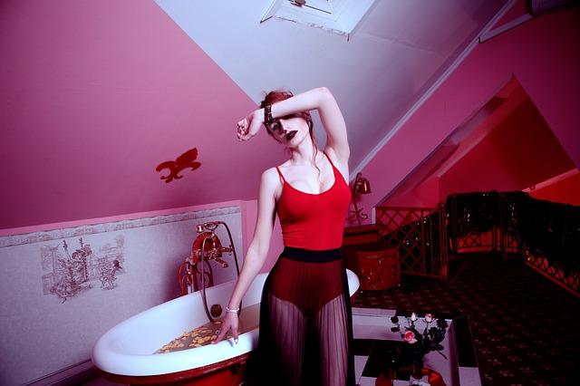 Žena v sexy oblečení s výrazným mejkapom stojí pri vani