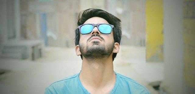 Muž v slnečných okuliaroch sa pozerá dohora
