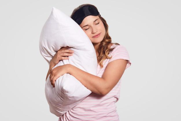 photo-european-woman-with-healthy-skin-leans-soft-pillow-wears-pyjamas-eyewear-head-poses-alone-white-has-sleepy-look-people-good-morning-concept_176532-8502